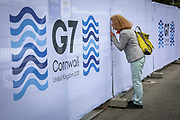 A woman peering through the security fencing around the G7 media centre on the 11th of June 2021 in Falmouth in Cornwall, United Kingdom. Security is extremely high around buildings across Cornwall this weekend for the G7 world leaders summit.