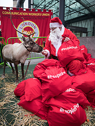 © Licensed to London News Pictures. 19/12/2016. London, UK. Santa Claus and his reindeer join Post office workers and supporters in protest outside the Department for Business, Innovation & Skills. Crown Post Offices are being affected during a five day strike by the Communication Workers Union's 3,000 staff at 300 high street branches in a dispute over branch closures, pensions and job losses. Photo credit: Peter Macdiarmid/LNP