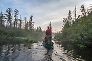 Brule River fishing guide Damian Wilmot poles upstream on the Brule near Lake Nebagamon, Wisconsin with angler Matson Holbrook in a 1900-era Joe Lucius guide canoe Wilmot meticulously restored over the course of two years.