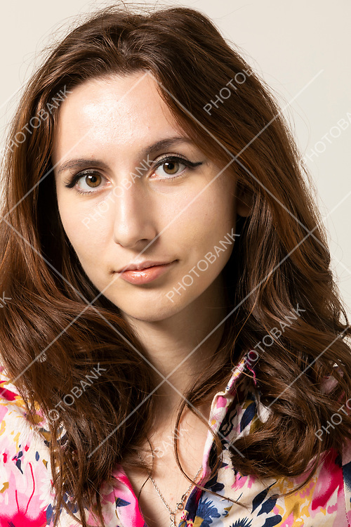 Portrait of young woman with long wavy hair. She looks straight into the room, detail of just her face