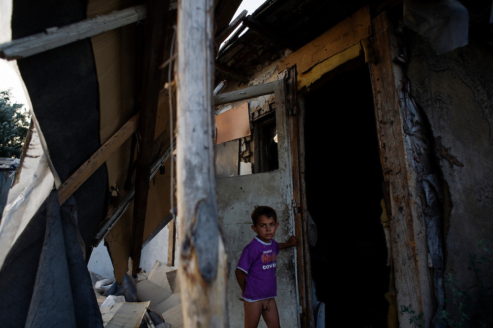 A boy plays in an abandoned house a few days before the entire camp is destructed by the city. Nova Gazela.