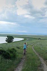 woman riding a bicycle by a lake in New Mexico