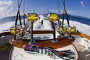 Heavy tackle and lures in fighting chair of running custom sport boat.