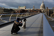 As the UK government announces further Coronavirus-related restrictions to its citizens, with the immediate closure of pubs, cafes, gyms and cinemas, and the worldwide number of deaths reaching 10,000 with 240,000 cases, 953 of those in London alone, dog walker Dan photographs his clients poodle with a background of St. Pauls Cathedral at the end of an unusually quiet Millennium Bridge, on 20th March 2020, in London, England.