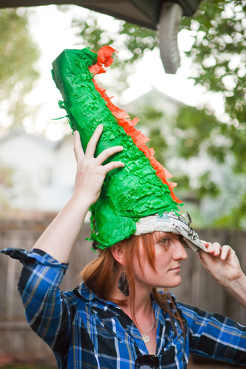 A young woman wears the tail of a dinosaur pinata as a hat in a front yard in Boulder, Colorado.