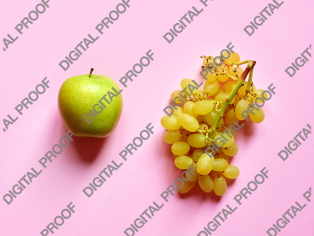 Green apple and bunch of green grapes isolated in studio against a pink background viewed from above