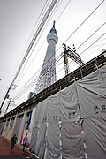 Outside Narihirabashi station, Tokyo Sky Tree, Tokyo, Japan, October 30, 2011. Scheduled to open to the public 22 March 2011, the Tokyo Sky Tree broadcasting tower is the tallest freestanding tower in the world at 634m high. On the 30 October 2011 the tower's 350m high viewing platform was opened to members of the media.