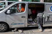 Two workmen parked in their company van, check messages and organise tools in the rear of their vehicle, in the City of London, the capitals financial heart, on 25th September 2018, in London, England.