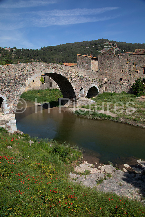 Scene of the stone bridge across the river in the medieval village of Lagrasse, Languedoc-Roussillon, France. Lagrasse is known as one of the most beautiful French villages. It lies in the valley of the River Orbieu.