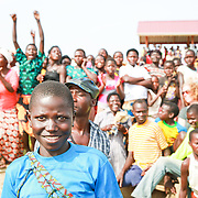 CAPTION: A spectator beams with delight as a crowd watched the spectacle that is the Kaberamaido Boat Race. LOCATION: Lake Kyoga, Abrepoli, Kaberamaido District, Uganda. INDIVIDUAL(S) PHOTOGRAPHED: Unknown; multiple people in the background.