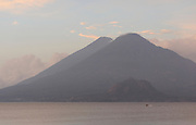 Early morning view across Lake Atitlan from Panajachel. A motor boat passes in front of Volcan Toliman, 3153m, and, behind it,  Volcan Atltlan, 3525m. The hill in front is Cerro de Oro. Panajachel, Republic of Guatemala. 04Mar14.