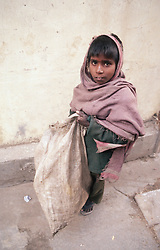 Young boy at work carrying sack,