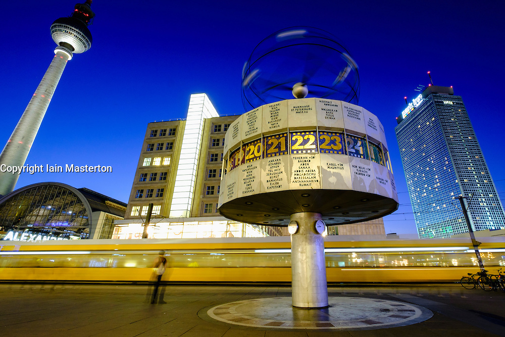 Night view of World Clock and tram at Alexanderplatz in Mitte Berlin Germany