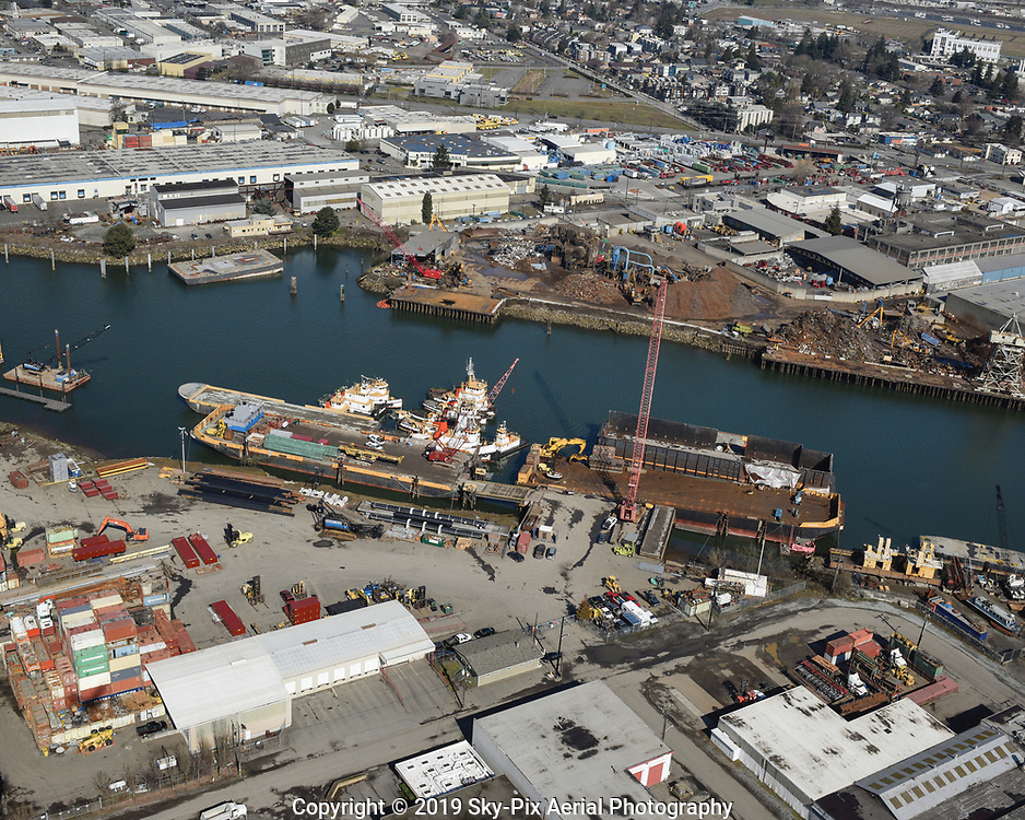 Aerial view of a marine towing, stevedoring and freight operations terminal, across the Duwamish River from a scrap iron and metal recycling facility.