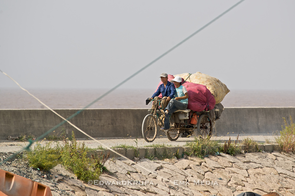 Couple on a makeshift three wheeled motorized bike transporting a large load by South China Sea.
