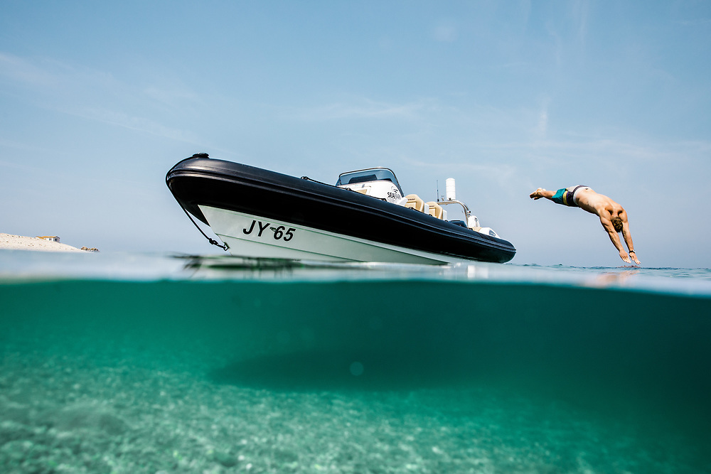 Person diving off a rib boat into the turquoise, calm water at the Ecrehous, a paradise beach destination, off the coast of Jersey, CI
