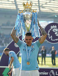 Manchester City goalkeeper Ederson poses with the trophy after winning the match