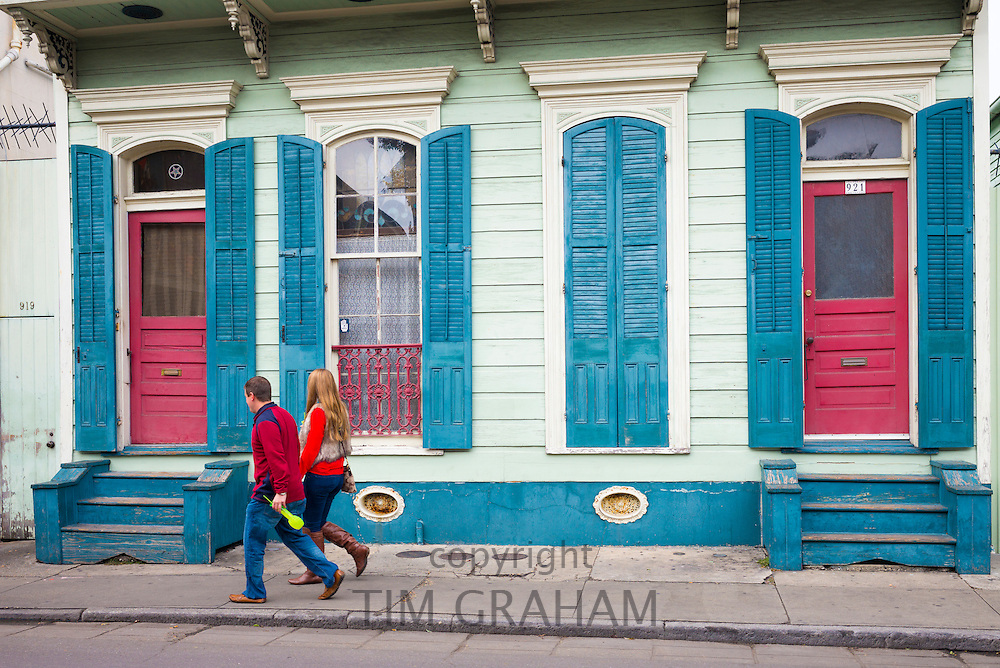 Couple passing bright color houses along Lower Bourbon Street in French Quarter of New Orleans, Louisiana, USA