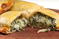 Spinach empanada fill close up.  The Empanada is a pastry turnover filled with a variety of savory ingredients and baked or fried.