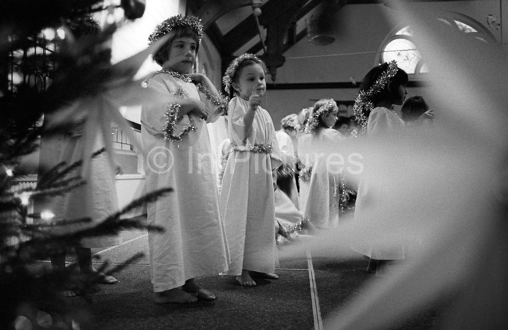 Seen through a stage star and the branches of a Christmas tree, two four year-old girls look excited during their playgroup's Christmas nativity play in a local church. It is a few weeks before Christmas and the local children have come to act out the Christian message of Jesus' birth by taking on roles of all the central characters plus those of the stable animals, three kings and angels who wear white gowns and tinsel in hair and around waists. This girls happy to be on stage in front of so many mums and dads.