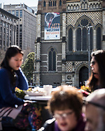 """People enjoy an outdoors cafe in Federation Square in the center of Melbourne, Australia. In the distance is St. Paul's Cathedral, which has posted a large sign expressing support for refugees -- """"Let's fully welcome refugees"""" (August 20, 2017)"""