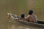 Huaorani Indians using dugout canoes. They bath from them too to get away from the muddy banks.<br /> Bameno Community. Yasuni National Park.<br /> Amazon rainforest, ECUADOR.  South America<br /> This Indian tribe were basically uncontacted until 1956 when missionaries from the Summer Institute of Linguistics made contact with them. However there are still some groups from the tribe that remain uncontacted.  They are known as the Tagaeri & Taromenane. Traditionally these Indians were very hostile and killed many people who tried to enter into their territory. Their territory is in the Yasuni National Park which is now also being exploited for oil.
