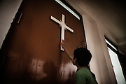 A refugee young boy from Kandmahal district kisses the cross during the prayer at Peyton sahi relief comittee in Orissa's capital Bhubaneswar. Nov. 03, 2008.