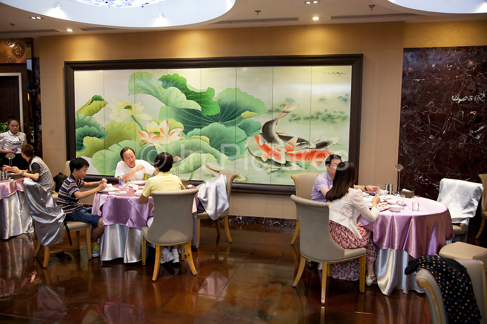 Customers in the main dining room. Quanjude roast duck restaurant in Wangfujing, Beijing. This is a Chinese restaurant known for its trademark Peking Roast Duck and is known for being the best roast duck restaurant in China. Quanjude was established in 1864 during the Qing Dynasty under the reign of the Tongzhi Emperor. Although Peking Duck can trace its history many centuries back, Quanjude's heritage of roast duck preparation - using open ovens and non-smoky hardwood fuel such as Chinese date, peach, or pear to add a subtle fruity flavor with a golden crisp to the skin, was originally reserved for the imperial families.