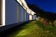 Beautiful modern house by night, view from the lawn