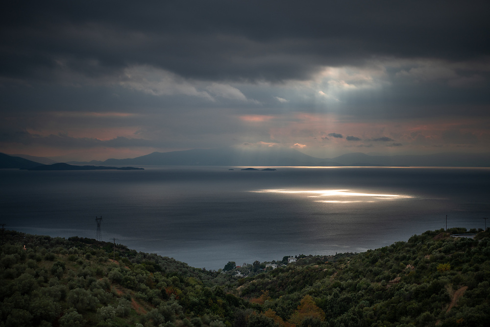 Sunrays hitting the water through dark and cloudy sky