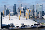 An aerial view from an Emirates Air Line cable car of showing the O2 Arena on the Greenwich Peninsular and the distant London Docklands, on 11th August 2021, in London, England.