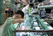 Computer seller asleep inside e-plaza digital square shopping mall. Zhongguancun or Zhong Guan Cun, is a technology hub in Haidian District, Beijing, China. It is situated in the northwestern part of Beijing city. Zhongguancun is very well known in China, and is often referred to as China's Silicon Valley. This is Beijing's computer district with numerous tech companies offices situated here amongst the many malls which sell electronics and electrons equipment of all kinds. The tech park started as a small office where two decades ago some students from a nearby university decided that computer equipment may be a thing of the future so set up a small company. It has expanded in this time to  cover many square kilometres.