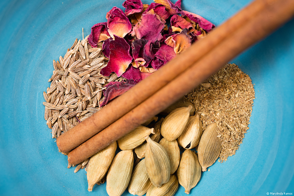 Ingredients for advieh, a middle eastern dried spice mix consisting of cinnamon, cumin, cardamom, golpar, and rose petals.