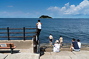people cooling off Tokyo Bay with Sarushima Island at at Umikaze park, Yokosuka