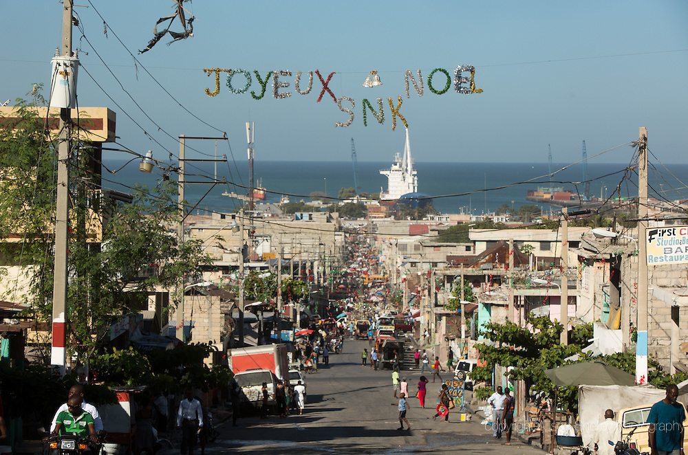 A Christmas banner hangs over a road in the Bel Air neighborhood of Port-au-Prince, Haiti, as seen from the grounds of Notre dame du Perpetuel Secous Catholic church, January 4, 2015.  Behind is the city port, which was severely handicapped in 2010 quake.