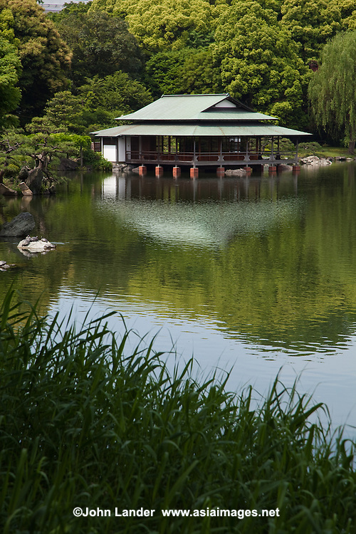 """Ryotei Teahouse - This sukiya-style teahouse was built projecting out onto the pond, giving the gardens a true Japanese atmosphere. The open-walled teahouse was originally built by the Iwasakis.to host British dignitary Marshall Kitchener who visited Japan in 1909. It survived earthquake and war, still standing today. It was designated a historical.structure by the Tokyo Metropolitan Government in 2005. Kiyosumi Teien Garden was the site of the residence of the Edo Period business magnate, Kinokuniya Bunzaemon. Later it became the residence of the Edo of the Lord of Sekiyado castle, Shimofusa-no-kuni the period when the basic form of the garden came into existence.  In 1878,  Iwasaki Yataro, chose this property to use a garden for the entertainment of important guests. After the design and construction phases ended, the garden opened in 1880 under the name of """"Fukagawa Shimbokuen."""" In later years, the waters of the Sumida River were brought into the grounds to make the pond. Hills and waterless waterfalls were constructed and famous rocks from all over Japan were brought in to embellish the garden. The garden was completed in the Meiji Period and developed into a famous strolling garden centered around a large pond."""