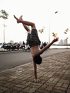 A Vietnamese kid does a handstand with one hand on the sidewalk beside West Lake, Hanoi, Vietnam, Southeast Asia