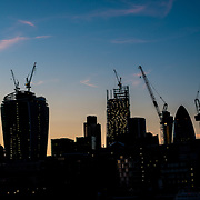 A silhouette at dusk of some of the new skyrises being constructed in the city of London.