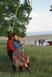 Couple  on a rope swing in a grassy field with horses