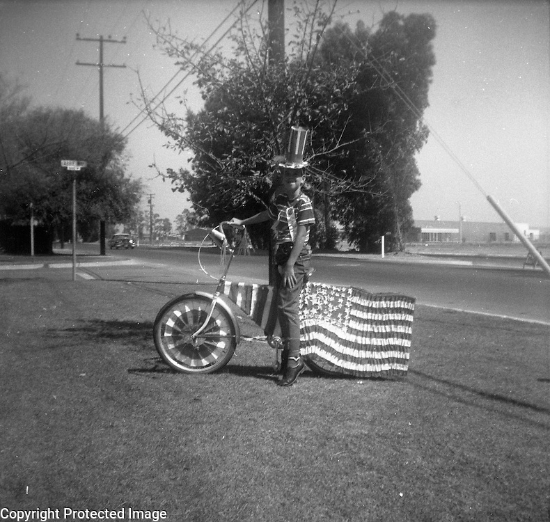 A boy dressed as Uncle Sam poses for a photo with his bicycle decorated with the stars and stripes and an American flag.