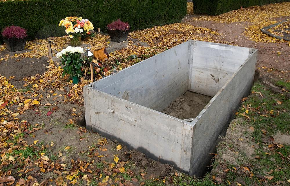Nederland Hoogvliet 29 oktober 2007 .Grafdelvers maken een nieuw graf op begraafplaats.  De bak waar de lift voor de kist in komt is geplaats .Foto David Rozing