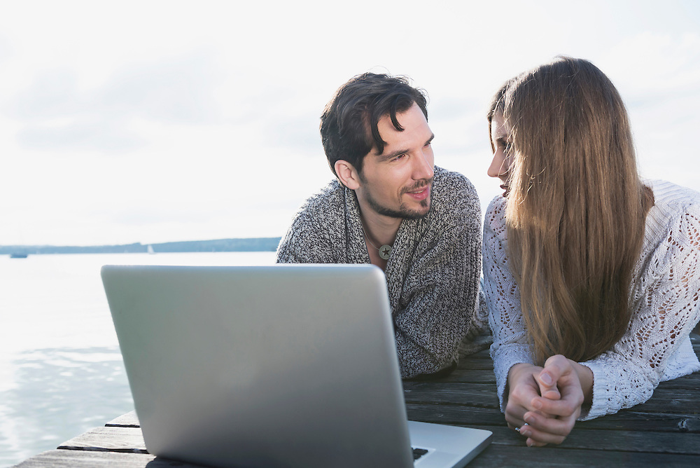 Young couple wooden jetty laptop computer