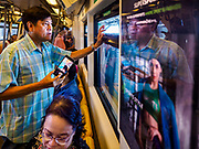 06 DECEMBER 2018 - SAMUT PRAKAN, THAILAND:  A rider on the newly opened BTS Skytrain east extension makes pictures with his smart phone on the first day of service on the line. The 12.6 kilometer (7.8 miles) east extension of the Sukhumvit Line of the Bangkok BTS Skytrain goes into Samut Prakan, a town east of Bangkok.  The system is now 51 kilometers long (32 miles), including the 12.6 kilometer extension that opened December 06. About 900,000 people per day use the BTS.     PHOTO BY JACK KURTZ