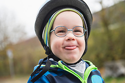 Close-up of playful boy in cycling helmet sticking tongue out of mouth