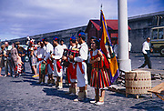 Folk group musicians wearing national costume line up to welcome cruise ship visitors, 1969, Funchal, Medeira