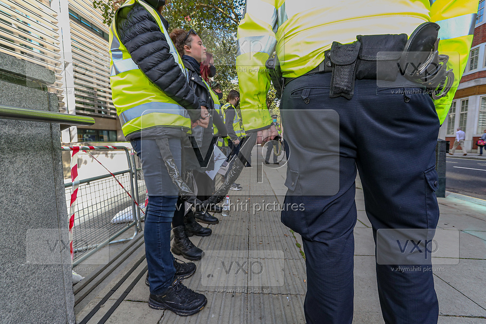 A police officer is holding the end of a chain in which a group of 10 Extinction Rebellion activists chained themselves outside Home Office in Marsham Street, central London on Friday, Sept 4, 2020.<br /> Marsham street remains both ways closed by the police. There are other Extinction Rebellion protests ongoing in London. Environmental nonviolent activists group Extinction Rebellion enters its 4th day of continuous ten days protests to disrupt political institutions throughout peaceful actions swarming central London into a standoff, demanding that central government obeys and delivers Climate Emergency bill. (VXP Photo/ Vudi Xhymshiti)