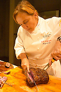 Dolly Irigoyen carving the roast beef on a big wooden carving board. The Dolly Irigoyen - famous chef and TV presenter - private restaurant, Buenos Aires Argentina, South America Espacio Dolli
