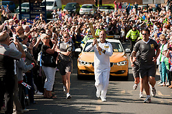 Olympic Torch reaches Sheffield Chapeltown/Ecclesfield/Parson Cross leg.<br /> Christopher Godwin Bearer 103 carries the torch out of Chapeltown and on up Ecclesfield Road past the Royal British Legion<br /> 25 June 2012.Image © Paul David Drabble