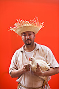 A man dressed in traditional Puerto Rican costume with chicken San Sebastian Festival in San Juan, Puerto Rico.