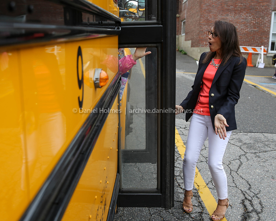 (8/30/17, HOPKINTON, MA) Teaching assistant Stacey Squatrito greets students on the bus on the first day of school at the Center School in Hopkinton on Wednesday. [Daily News and Wicked Local Photo/Dan Holmes]